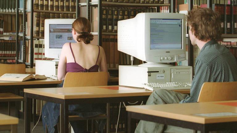 Zwei Studierende arbeiten an PCs in einer Hochschul-Bibliothek