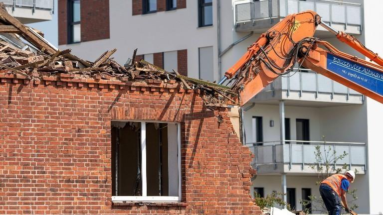 Ein altes Haus wird abgerissen von einem Bagger. Ein Bauarbeiter steht neben dem Bagger.