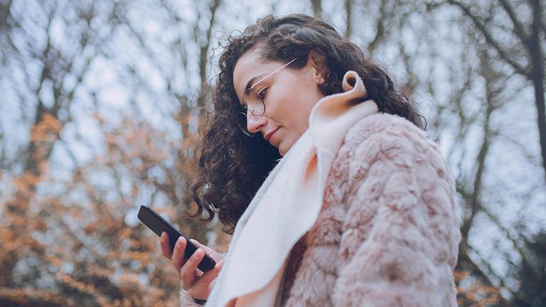 Eine junge Frau mit Jacke und Schal schaut auf ihr Smartphone, hinter ihr stehen Bäume. Es ist Herbststimmung.