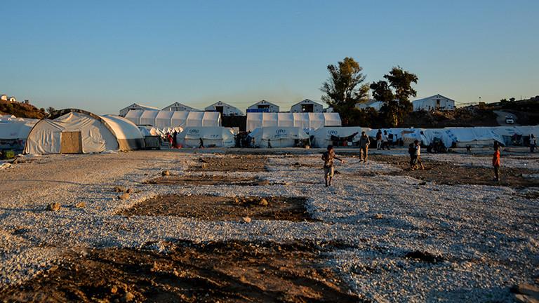 Momentaufnahme aus dem Flüchtlingslager Kara Tepe auf Lesbos; im Hintergrund sind Zelte, vorne laufen Kinder über eine geschotterte Fläche (11.10.2020)