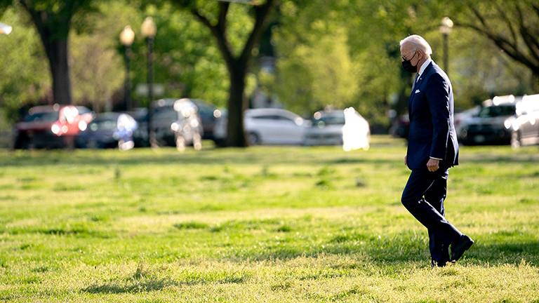 US-Präsident Joe Biden geht über eine Wiese. Er trägt einen dunklen Anzug und eine Mund-Nase-Maske (16.04.2021)