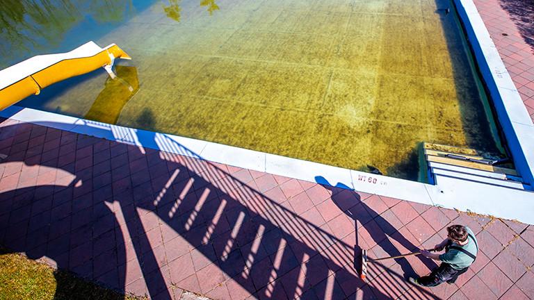 Blick auf ein Schwimmbecken im Freibad ohne Besucher; es scheint Herbst. Im Bild vorne kehrt ein Mann die Steine.