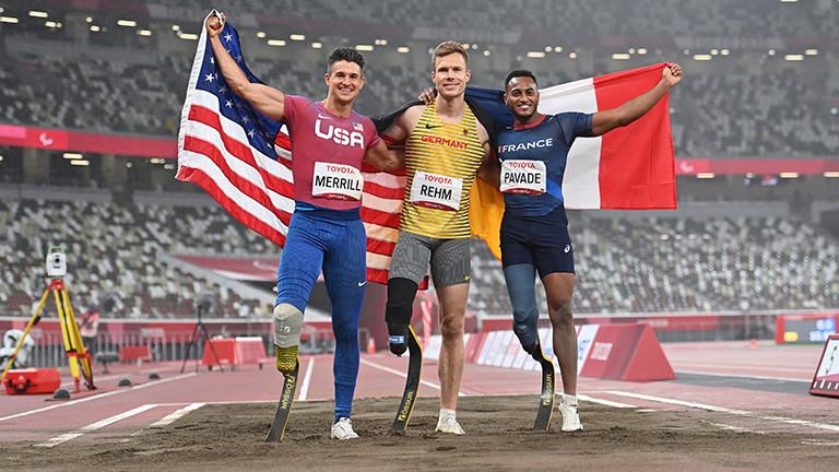 Der Weitspringer Markus Rehm holte in Tokio bei den Paralympics Gold. Er stehen zwischen dem Franzosen Dimitri Pavade (Silber) und dem US-Amerikaner Trenten Merrill (Bronze). Die drei haben die Arme übereinander gelegt und grinsen; Foto: dpa (1.9.2021)