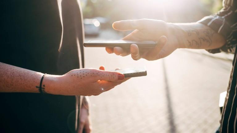 Zwei Personen halten ihre Smartphones übereinander.