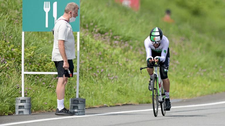 Sportdirektor Patrick Moster beobachtet einen Radprofi auf dem Fahrrad.