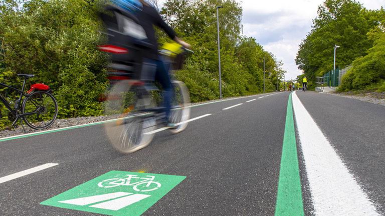 Auf dem Radschnellweg RS1, kurz für Radschnellweg Ruhr, fährt ein Fahrrad. Der Schnellweg ist eine breite Spur mit Linienführung ähnlich einer Straße.