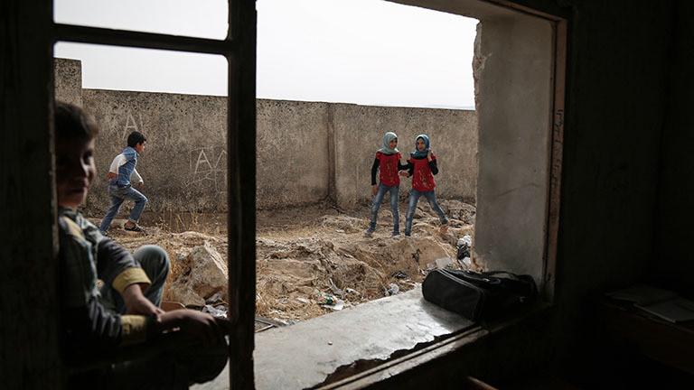 Syrische Schulkinder spielen vor dem Fenster eines Klassenzimmers einer Schule in Tur Laha an der syrisch-türkischen Grenze. Das Fenster ist kaputt. Die Kinder spielen auf Schuttresten; Foto: dpa