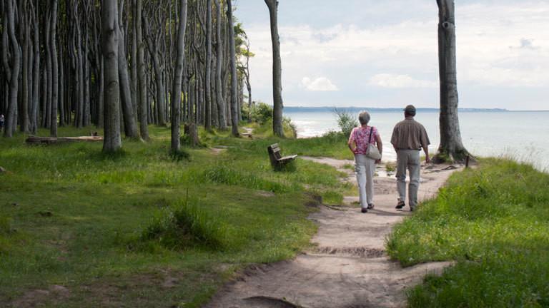 Zwei ältere Menschen gehen Hand in Hand am Strand entlang.