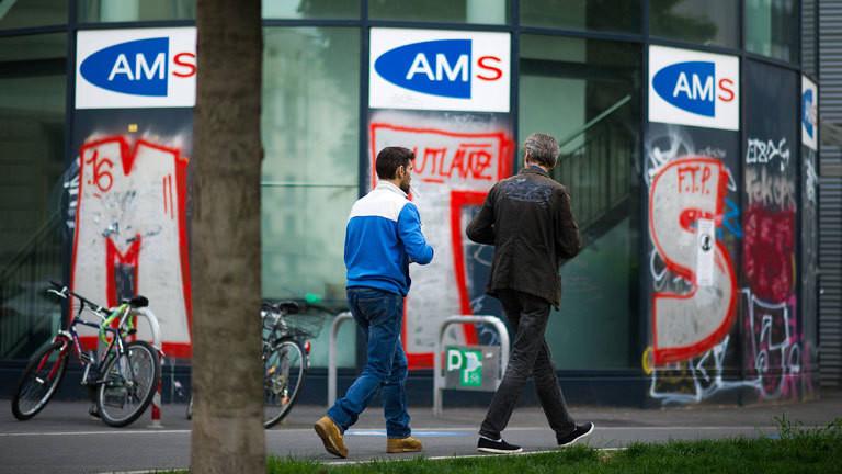 Zwei Männer laufen an einer Filiale des österreichischen Arbeitsmarktservice (AMS) vorbei.
