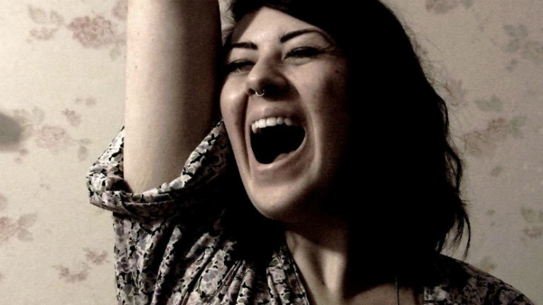 Eine Frau singt mit weit offenem Mund.