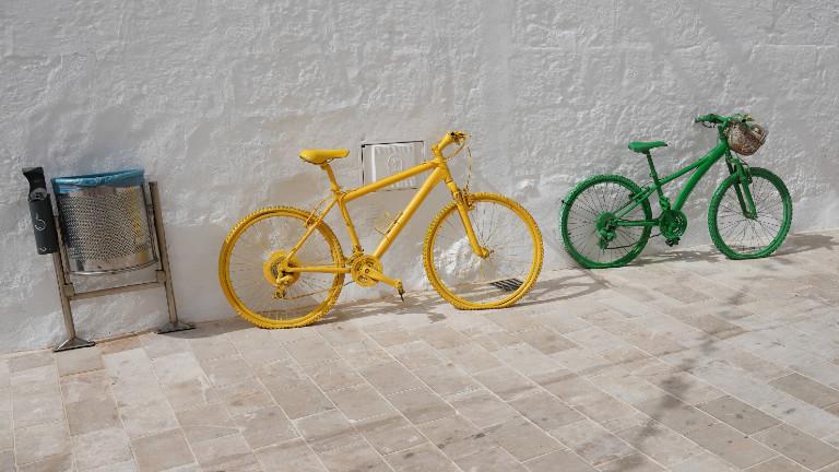 Ein gelbes und ein grünes Fahrrad lehnen an der Wand.