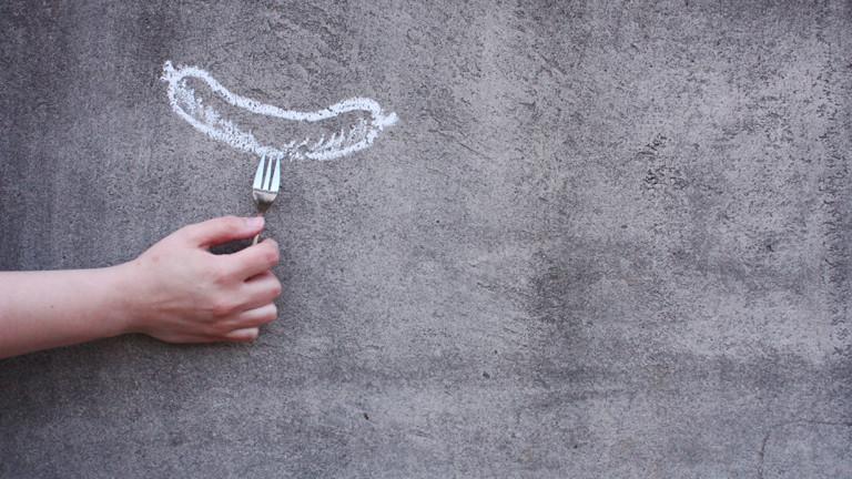 Eine Hand hält eine Gabel an eine Zeichnung mit einer Wurst