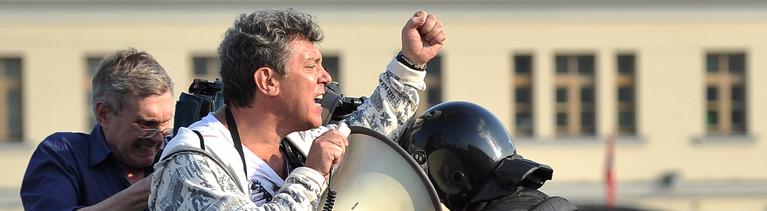 Polizisten ziehen Boris Nemtsow bei einer Kundgebung vom Podium