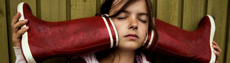 Ein Mädchen hält Gummistiefel an die Ohren