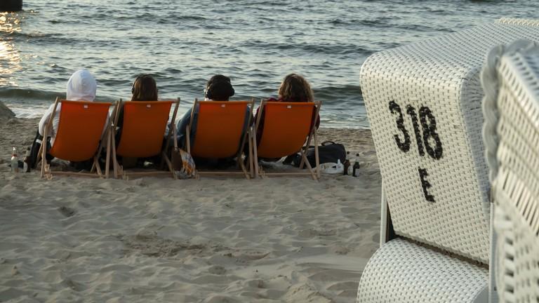 Vier Menschen sitzen in Liegestühlen am Stand mit Blick auf das Meer.