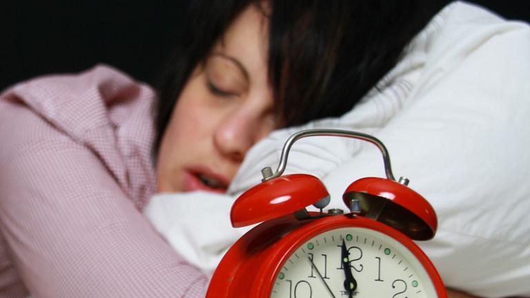 Eine Frau im Bett neben einem Wecker
