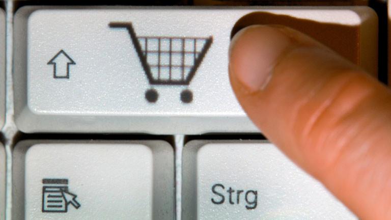 Finger tippt auf der Tastatur auf Einkaufswagen-Symbol