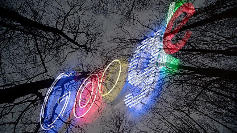 Das Google-Logo als Leuchtschrift vor toten Bäumen