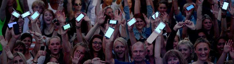 Zahlreiche Menschen nehmen am 28.07.2014 in Hamburg mit ihren blau leuchtenden Smartphones am offiziellen Light Up zum Blue Port Hamburg teil.