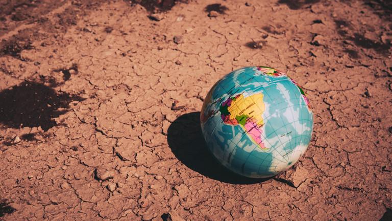 Ein Globus liegt auf trockener Erde