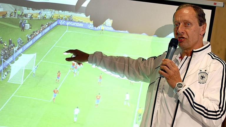 Helmut Krug zeigt auf einer Pressekonferenz der Bundesliga Schiedsrichter auf eine Leinwand