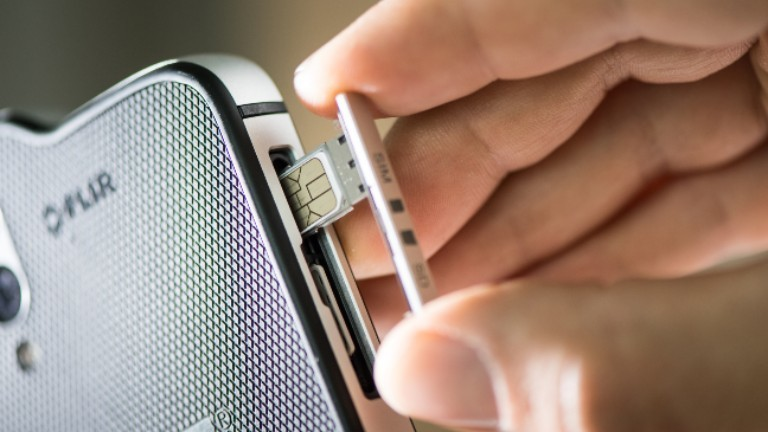 Eine SIM-Karte wird ins Handy gelegt
