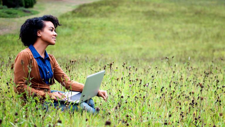 Eine Frau sitzt mit ihrem Laptop in einer Blumenwiese