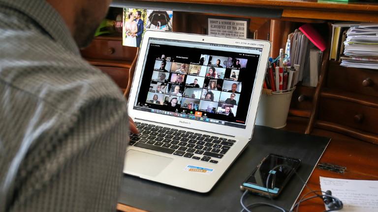 Mann sitzt vor dem Laptop mit einem geöffneten Videochatdienst