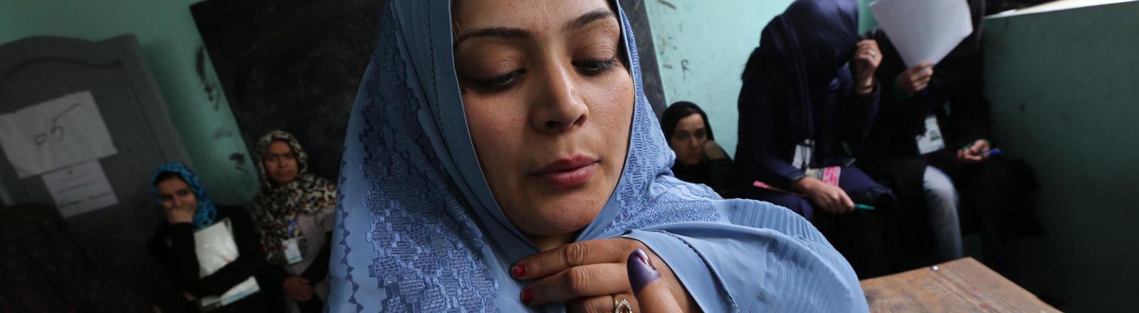 Eine afghanische Wählerin mit dem gefärbten Finger.