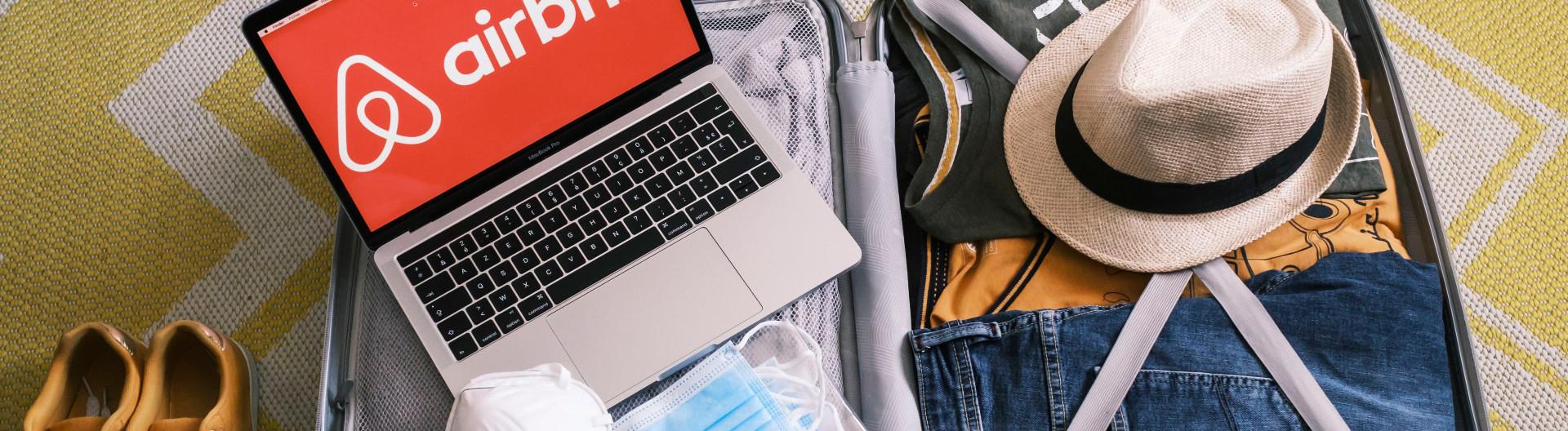 Gepackter Koffer mit Mundschutz und Laptop mit Airbnb-Logo