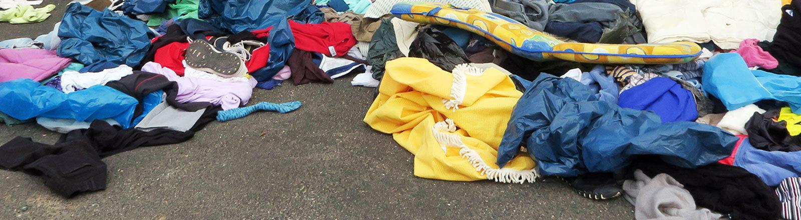 Altkleider liegen verstreut vor einem Sammelcontainer von Kolping International