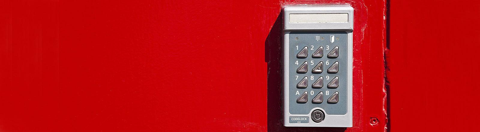 Ausschnitt einer roten Tür mit einem Codeschloss