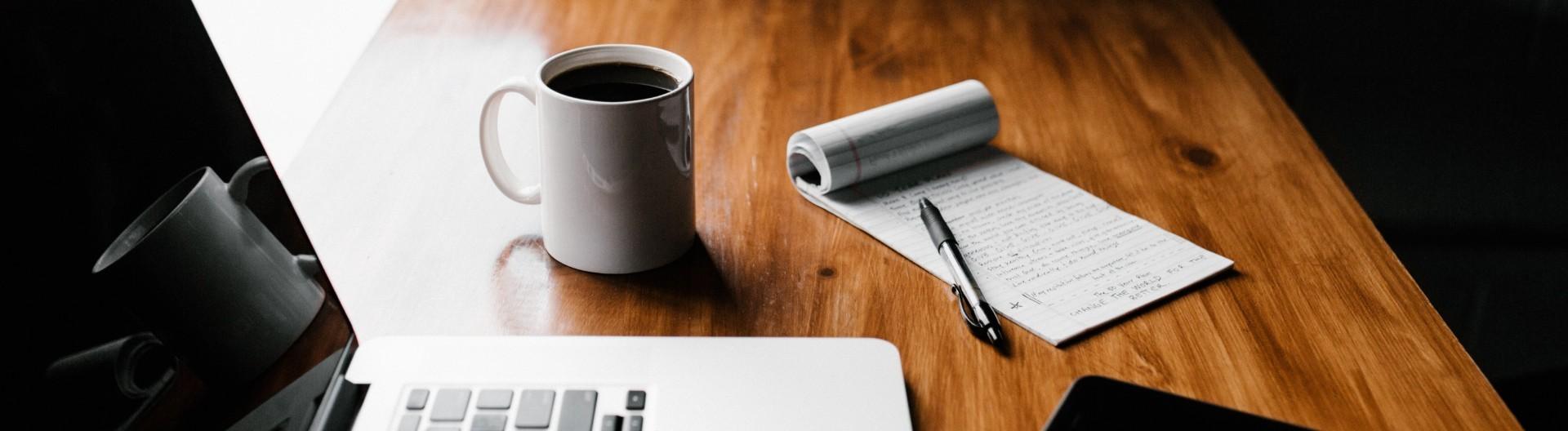 Laptop und Notizblock auf Schreibtisch