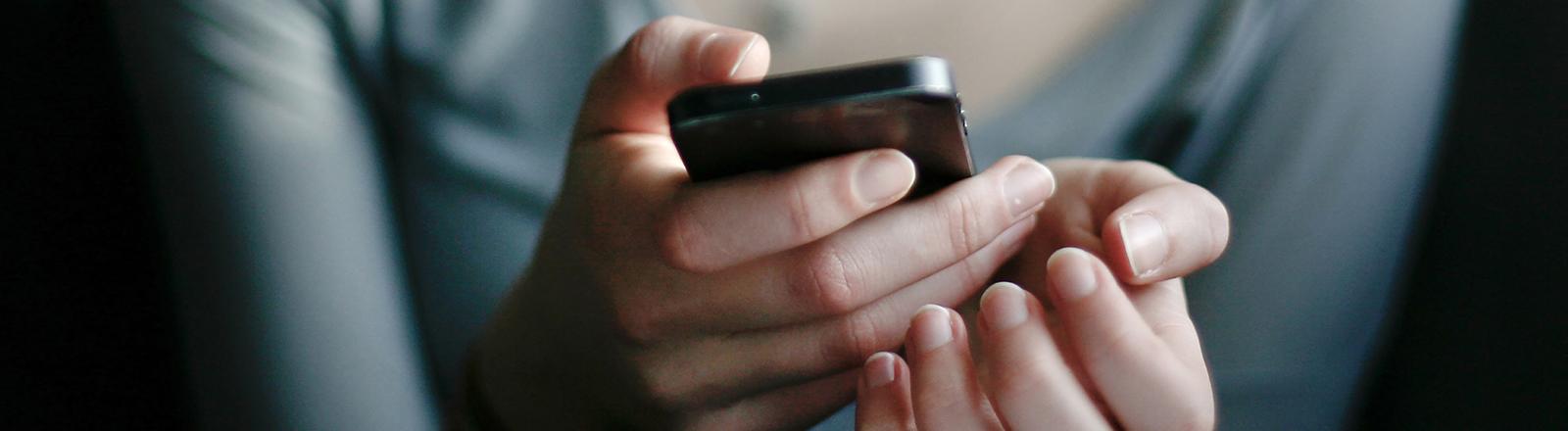 Junge Frau mit Smartphone in der Hand