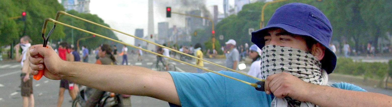 Ein vermummter Demonstrant zielt während einer Anti-Regierungs-Demonstration am 20.12.2002 in Buenos Aires mit seiner Schleuder auf Polizisten.