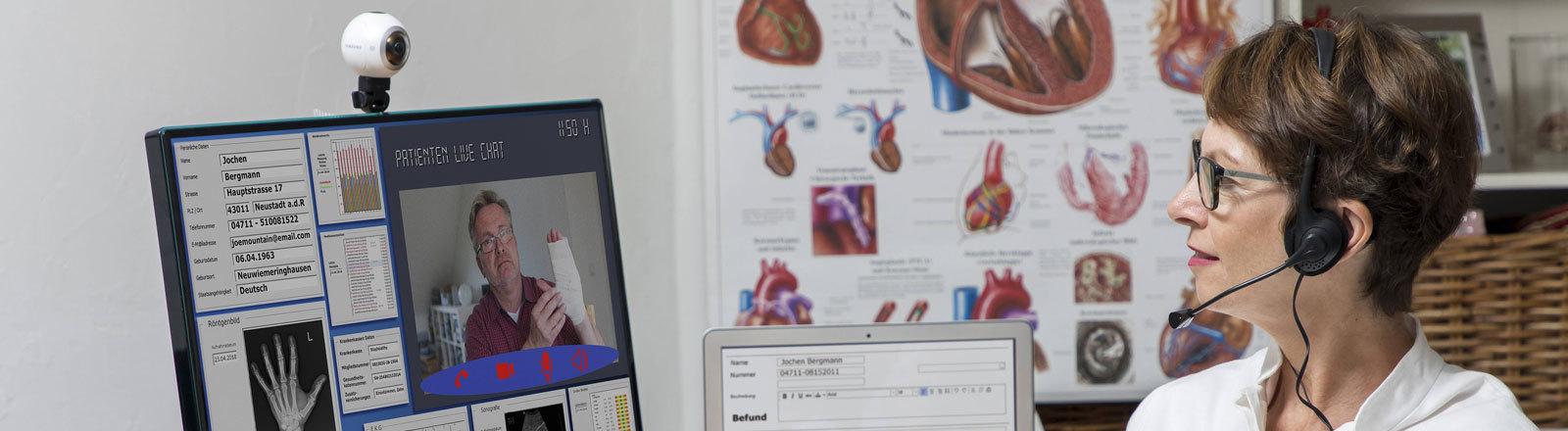 Symbolfoto zur Telemedizin, Ärztin in einer Praxis, kommuniziert mit dem Patienten über eine Webcam, Patientendaten und Befunde auf dem Monitor