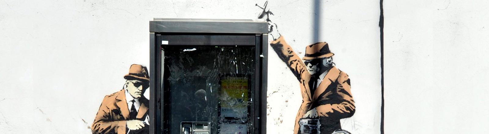 Banksy Streetart von drei Agenten, die eine Telefonzelle abhören