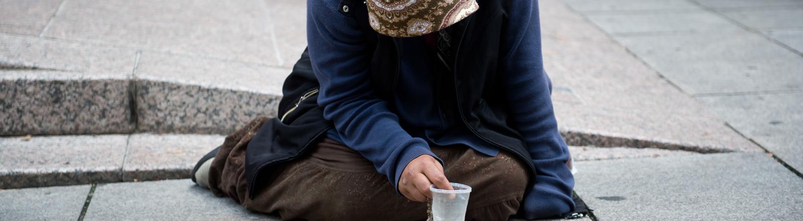 Eine Bettlerin in Berlin sitzt mit gesengtem Haupt auf der Straße.