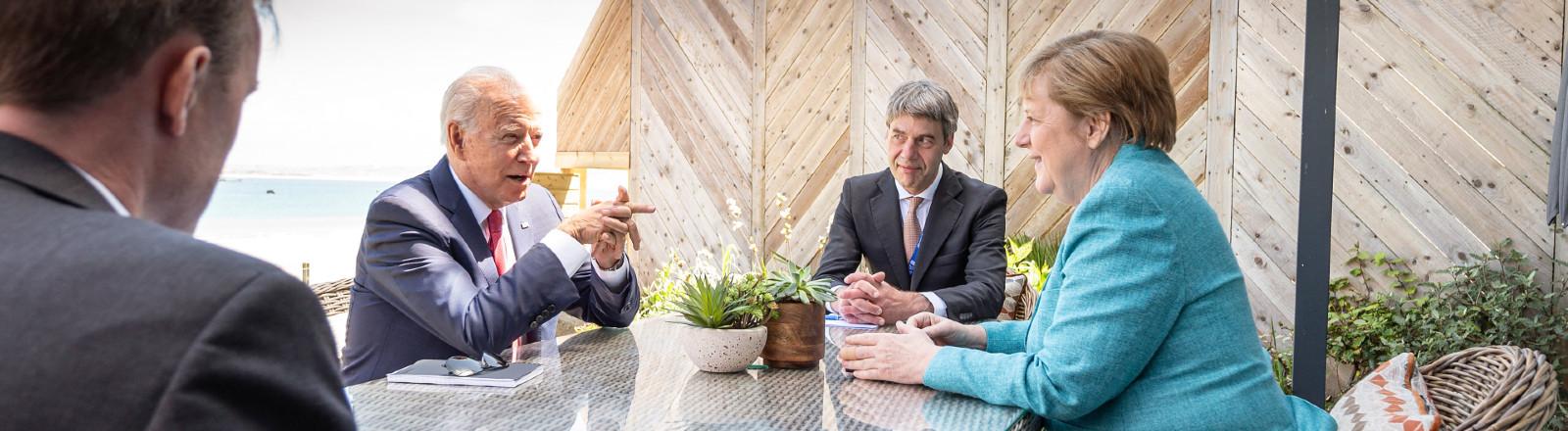 Bundeskanzlerin Angela Merkel (CDU) und US-Präsident Joe Biden (2.v.l.) sitzen am 12.06.2021 zu Beginn ihres Gesprächs am Rande des G7-Gipfels mit ihren außenpolitischen Beratern Jan Hecker (2.v.r.) und Jake Sullivan (l) zusammen.