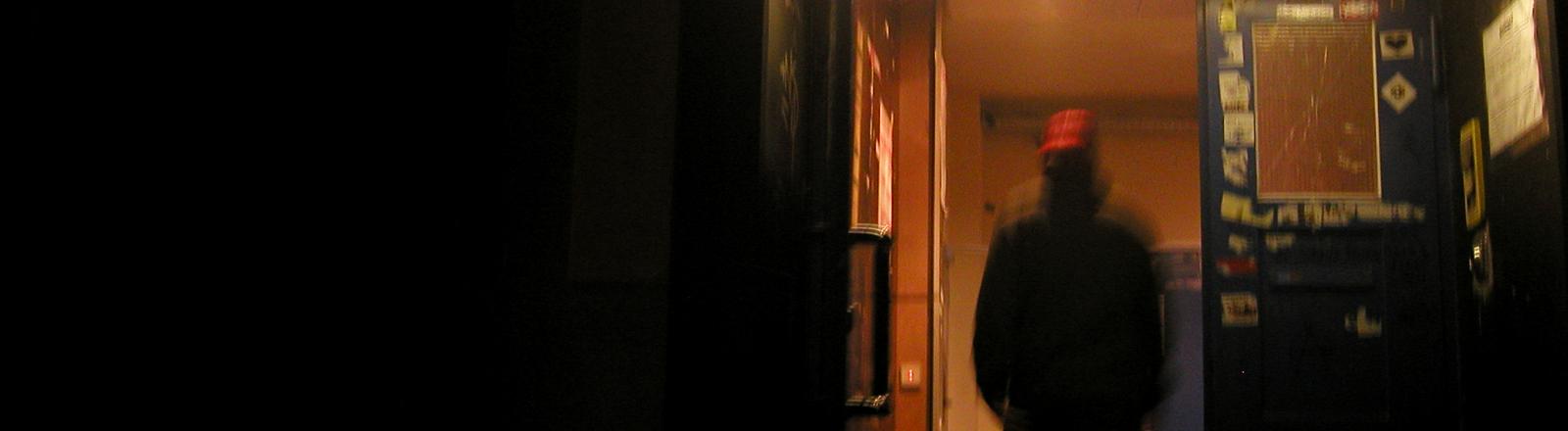 Mann steht in dunklem Türeingang.