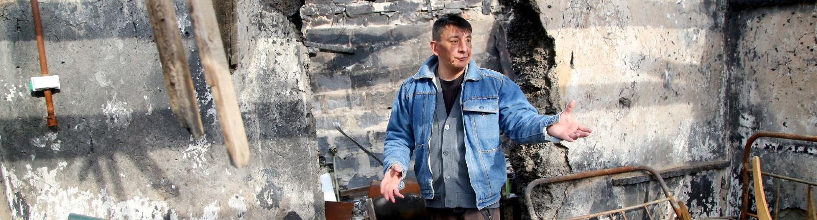 Ein Mann steht vor einem zerstörten Gebäude in einem Dorf in der Ostukraine