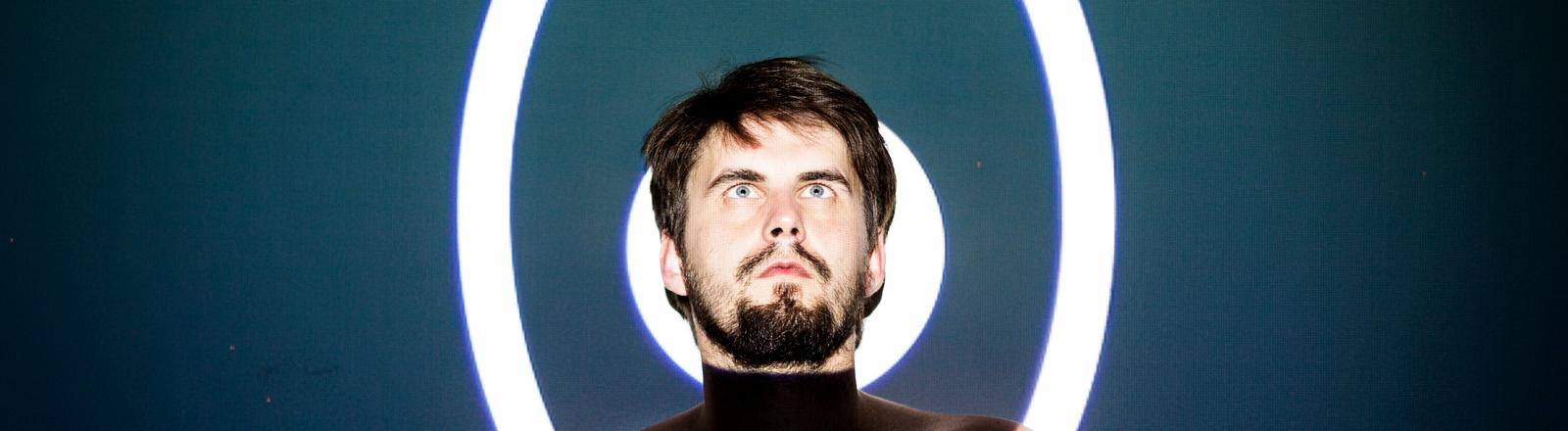 Ein Mann wird von zwei hellen Kreisen quasi durchleuchtet.