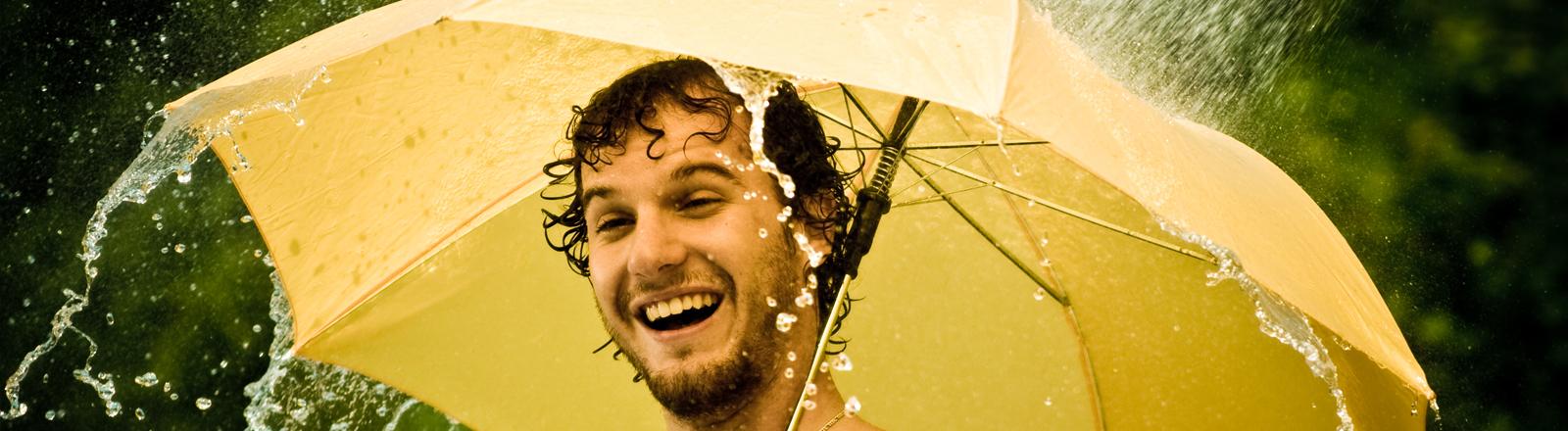 Ein Mann steht unter einem Regenschirm und duscht