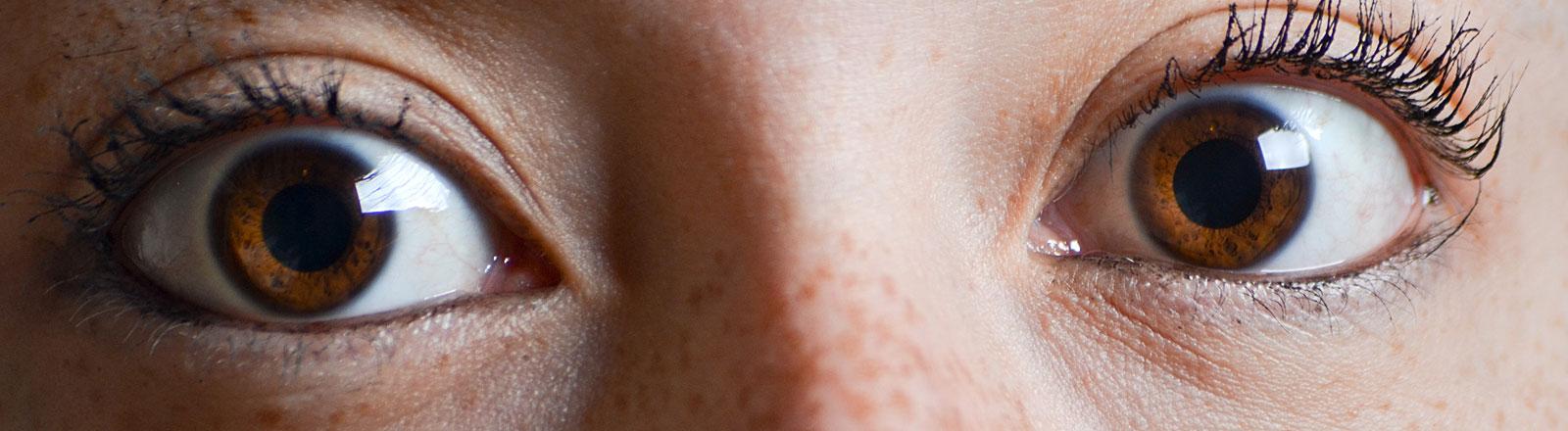 Frau reißt ihre braunen Augen auf