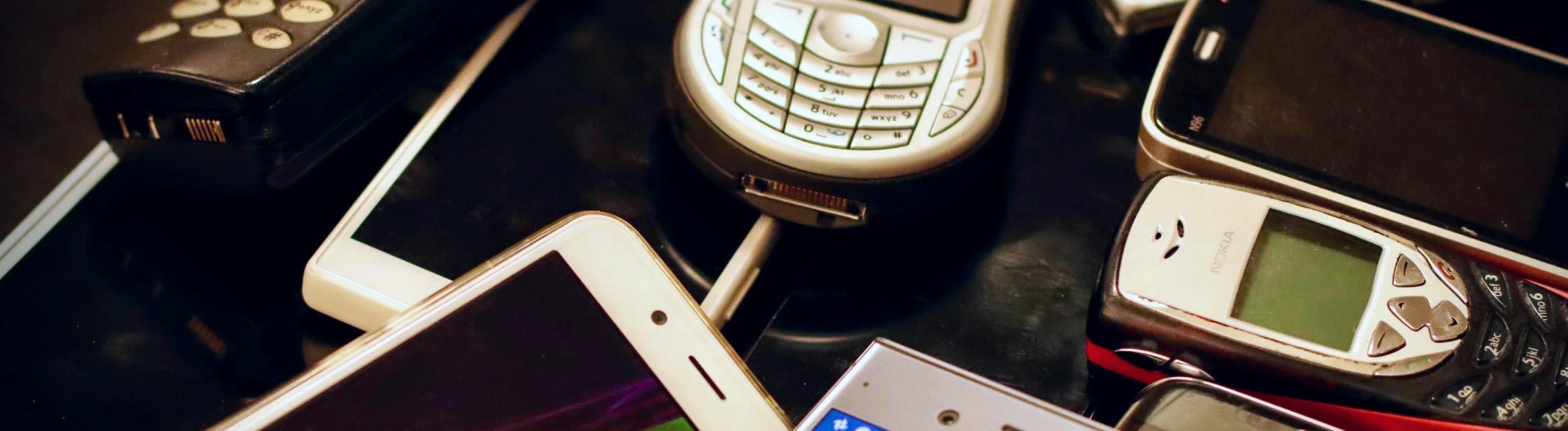 Alte Handys liegen auf einem Haufen.