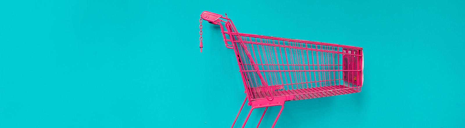 pinker Einkaufswagen vor türkisfarbener Wand