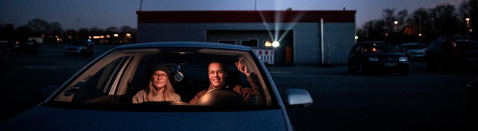 24.03.2020, Nordrhein-Westfalen, Essen: Zwei Besucher des Autokinos sitzen im PKW und gucken auf die Leinwand.