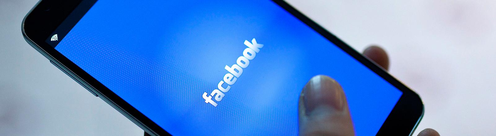 Eine Hand surft auf einem Smartphone-Screen bei Facebook