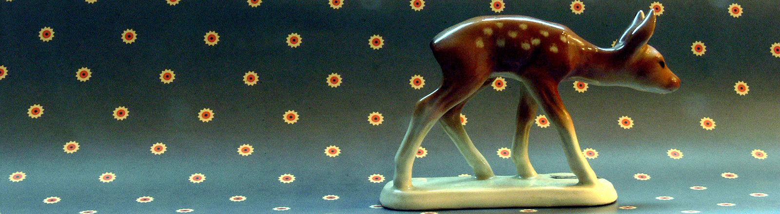 Kitschfigur Reh vor gepunkteter Tapete