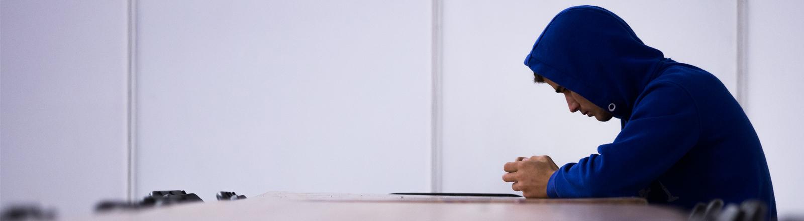 Ein Flüchtling schaut auf sein Mobiltelefon